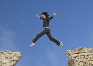 woman jumping between two rocks