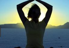 woman doing yogo on the seashore