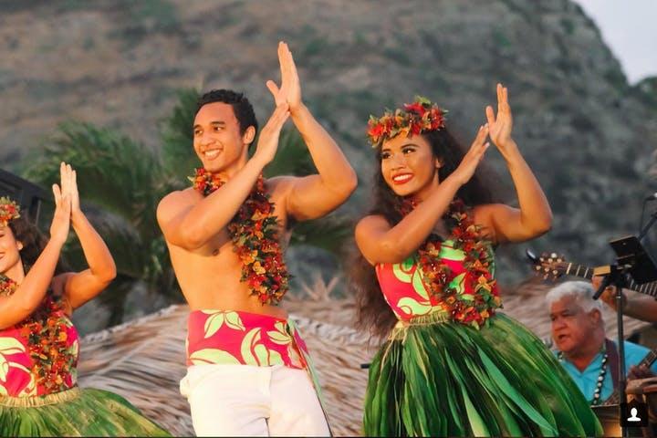 Fit man and woman dancing on Hawaiian attire